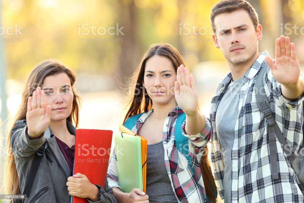 Three students gesturing stop in a park stock photo