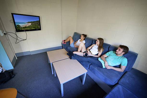 tres estudiantes en una dorm en un sillón mientras ve televisión - couch potato refrán en inglés fotografías e imágenes de stock