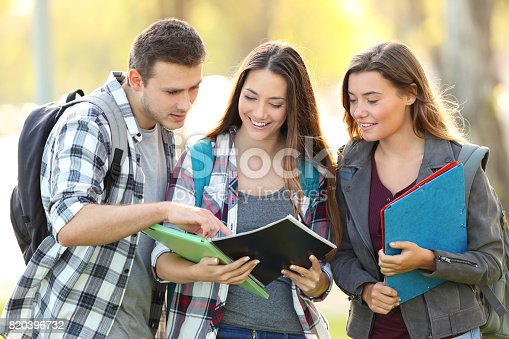 istock Three students learning reading notebook 820396732