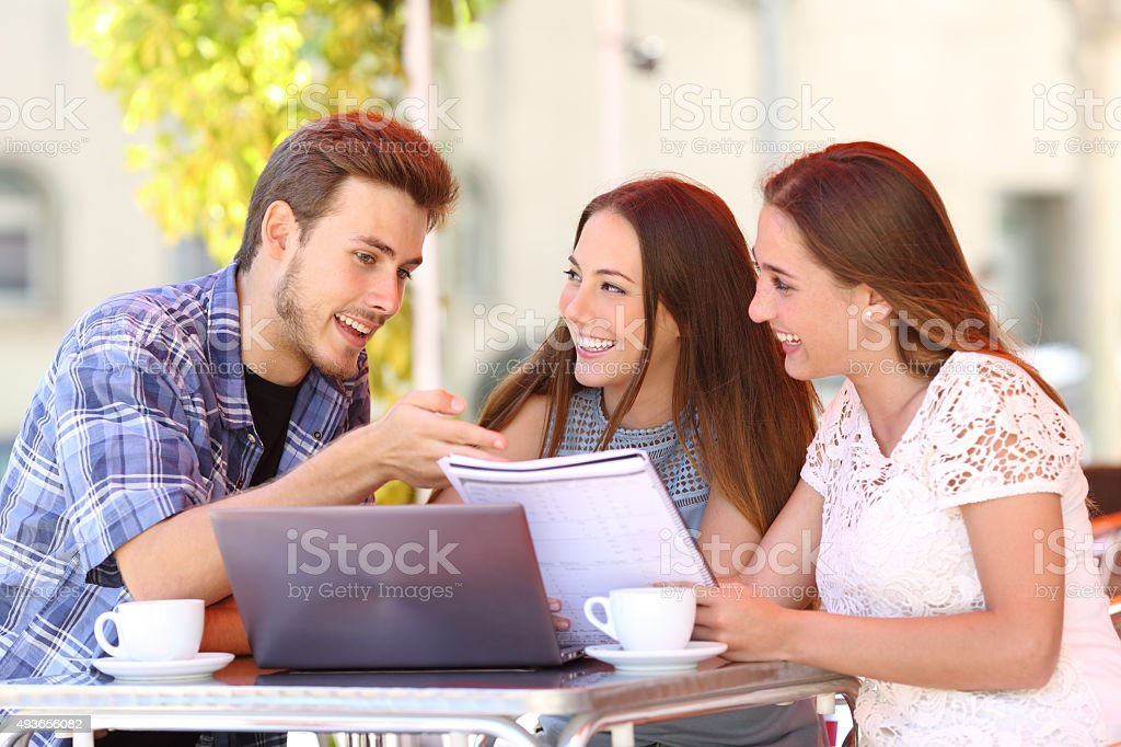 Three students studying and learning in a coffee shop stock photo