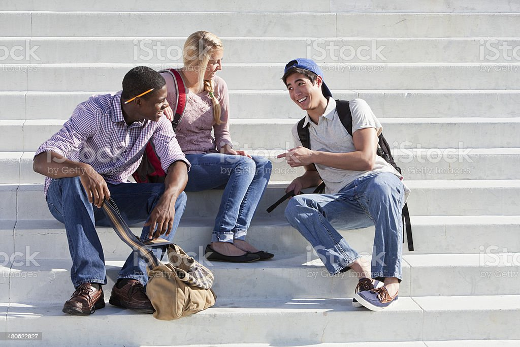 Three students talking on steps royalty-free stock photo