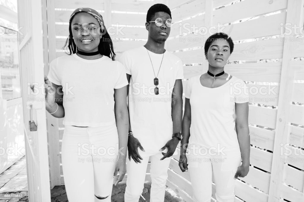 Three stylish african american friends, wear on white clothes against wooden background. Street fashion of young black people. Black man with two african girls. stok fotoğrafı