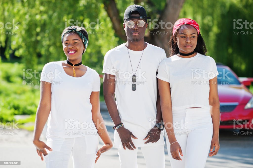 Three stylish african american friends, wear on white clothes against luxury red sport car. Street fashion of young black people. Black man with two african girls. stok fotoğrafı