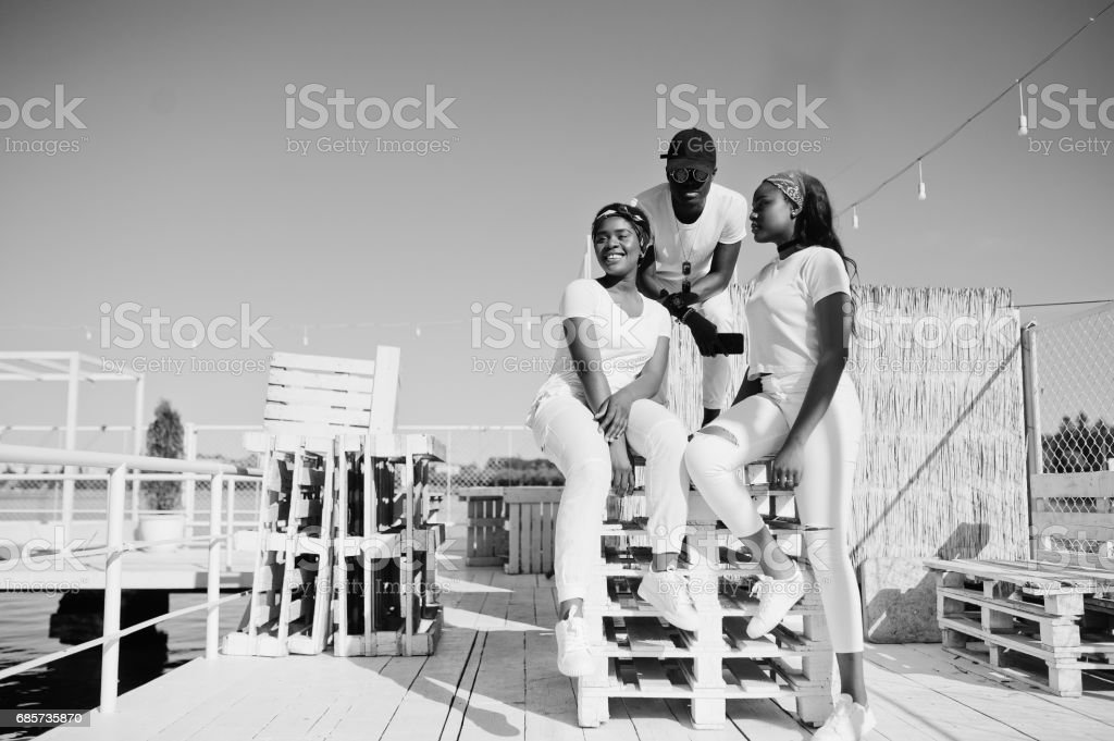 Three stylish african american friends, wear on white clothes at pier on beach. Street fashion of young black people. Black man with two african girls. royalty-free 스톡 사진