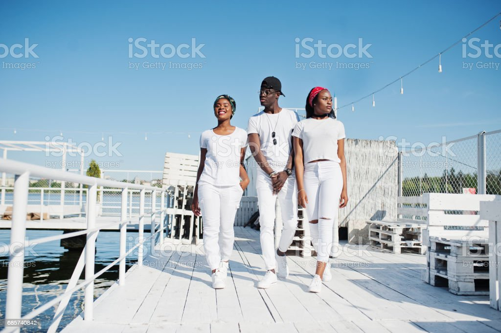 Three stylish african american friends, wear on white clothes at pier on beach. Street fashion of young black people. Black man with two african girls. stok fotoğrafı
