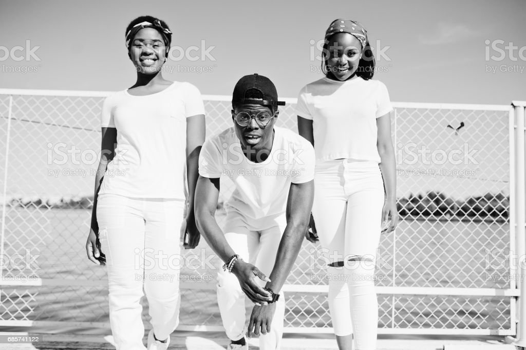 Three stylish african american friends, wear on white clothes at pier on beach against cage. Street fashion of young black people. Black man with two african girls. stok fotoğrafı