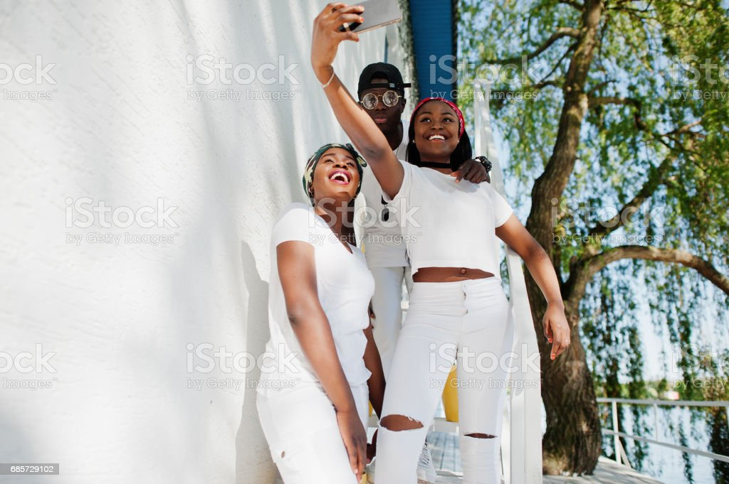 Three stylish african american friends, wear on white clothes making selfie. Street fashion of young black people. Black man with two african girls. 免版稅 stock photo