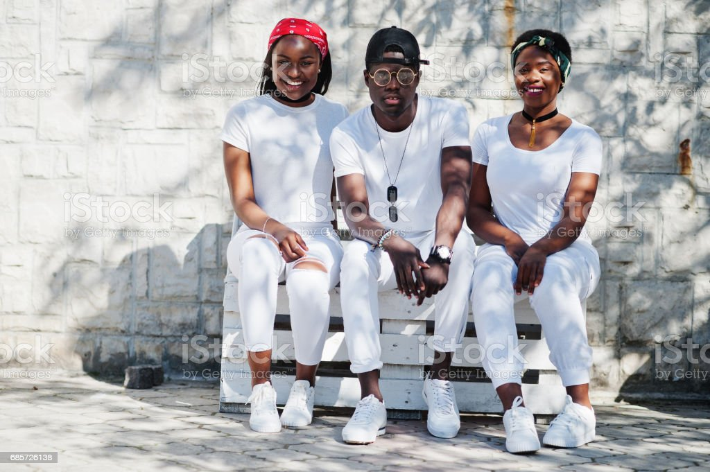 Three stylish african american friends, wear on white clothes sitting on bench. Street fashion of young black people. Black man with two african girls. 免版稅 stock photo