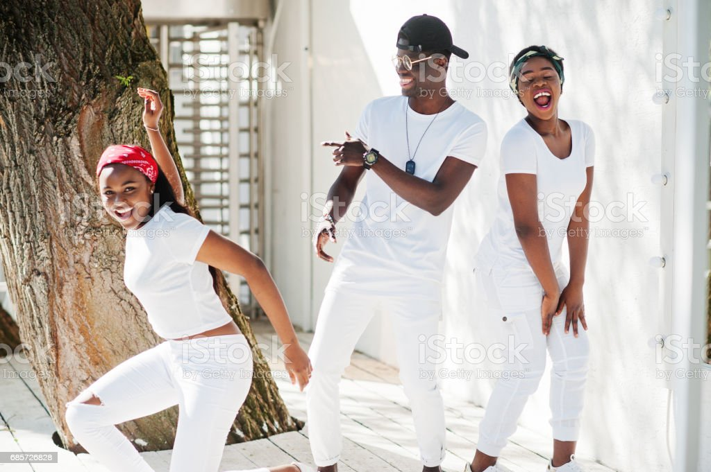 Three stylish african american friends, wear on white clothes. Street fashion of young black people. Black man with two african girls dancing gangsta rap style. stok fotoğrafı
