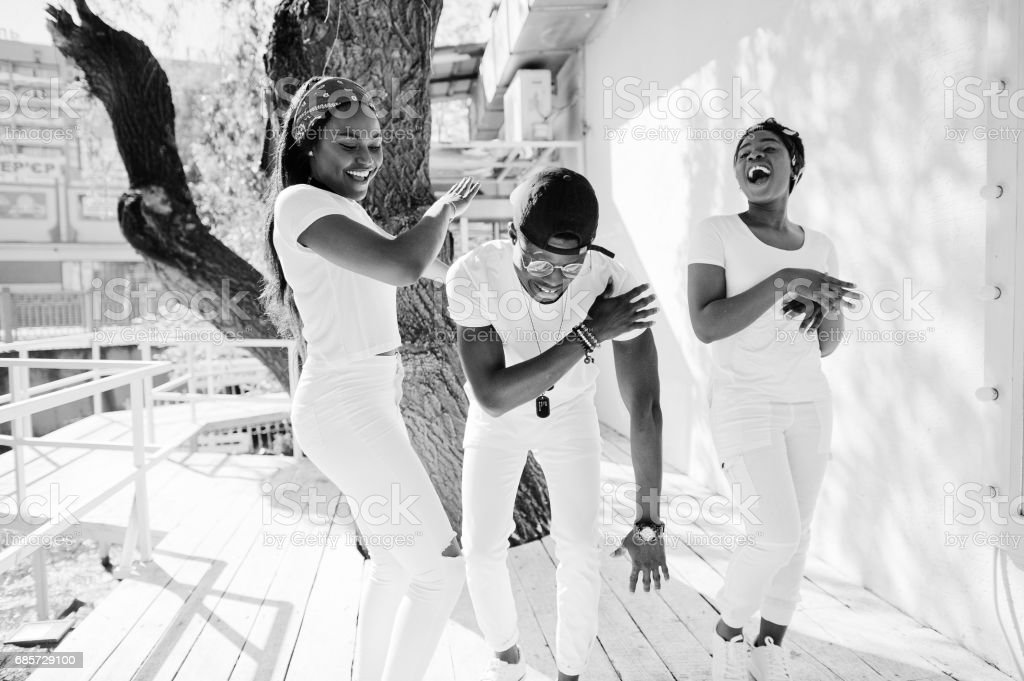 Three stylish african american friends, wear on white clothes. Street fashion of young black people. Black man with two african girls dancing gangsta rap style. royalty-free 스톡 사진