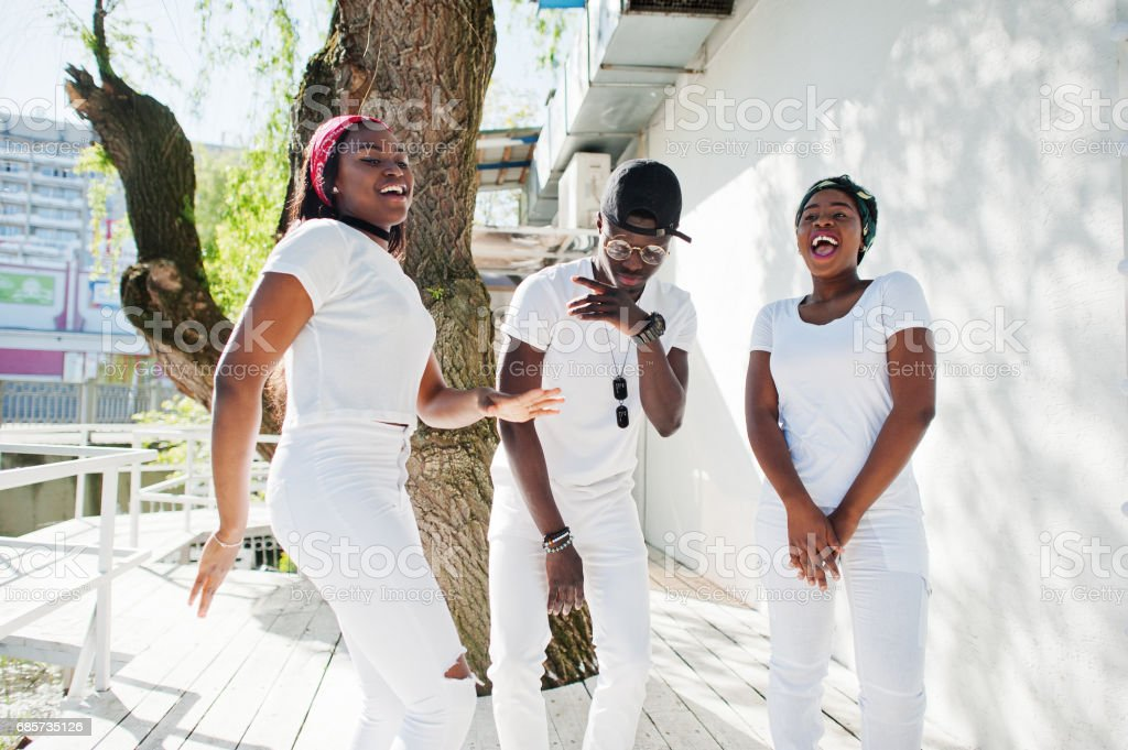 Three stylish african american friends, wear on white clothes. Street fashion of young black people. Black man with two african girls dancing gangsta rap style. foto de stock royalty-free
