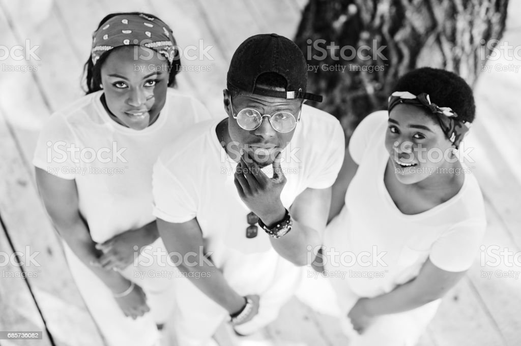 Three stylish african american friends, wear on white clothes. Street fashion of young black people. Black man with two african girls. View from above. stok fotoğrafı