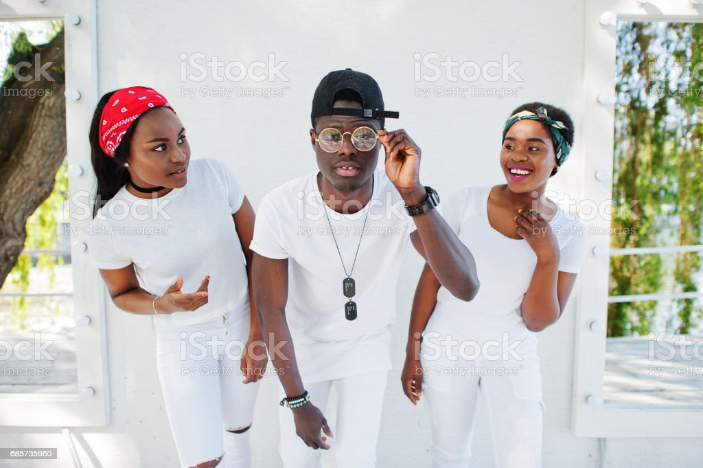 Three stylish and trendy african american friends, wear on white clothes against mirrors. Street fashion of young black people. Black man with two african girls. stok fotoğrafı