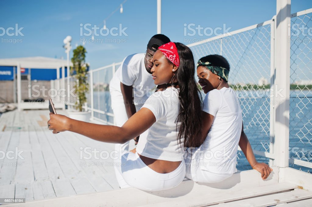 Three stylish and trendy african american people, wear on white clothes against lake on pier beach making selfie. Street fashion of young black friends. stok fotoğrafı