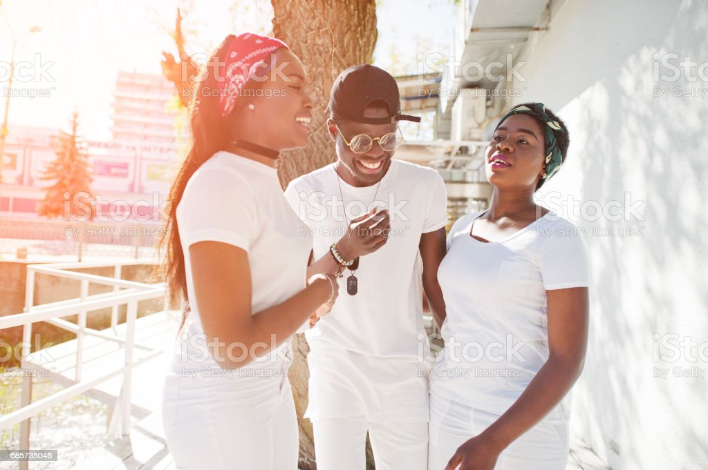 Three stylish cheerful african american friends, wear on white clothes. Street fashion of young black people. Black man with two african on sunshine. foto de stock royalty-free
