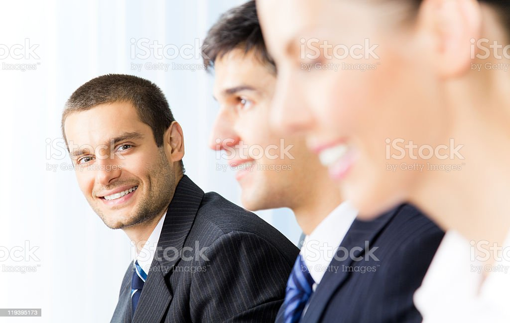 Three successful businesspeople at office, with selective focus on man royalty-free stock photo