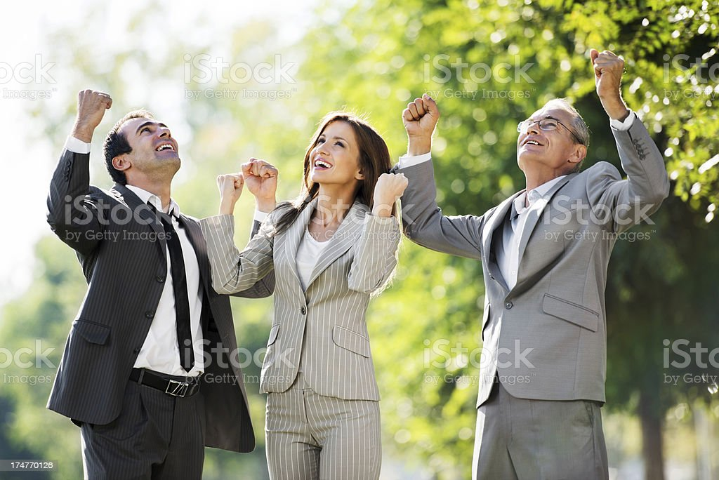 Three successful businesspeople with raised hands in park. royalty-free stock photo