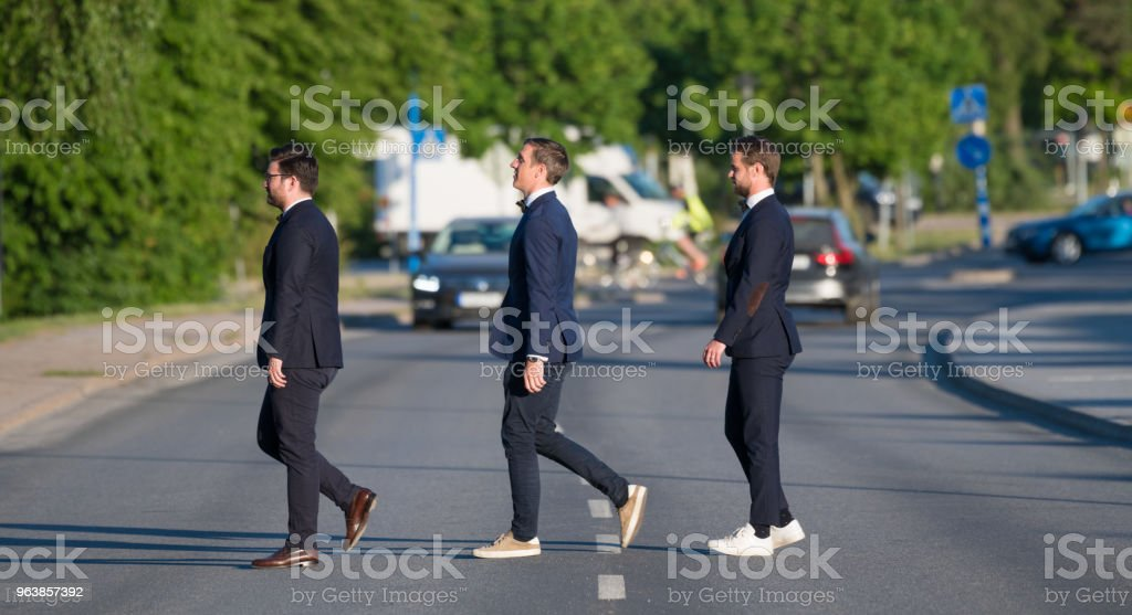 Three suits crossing street, in profile - Royalty-free Business Stock Photo