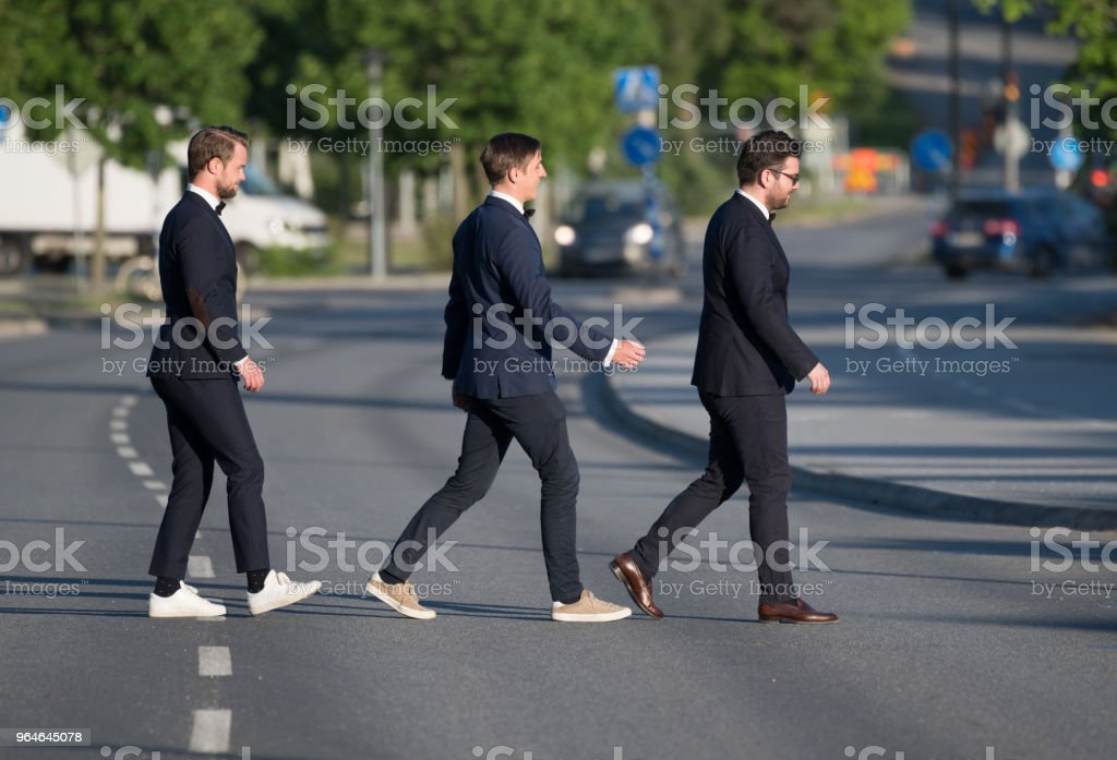 Three suits crossing street, in profile royalty-free stock photo