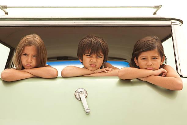 Three sullen children in back of estate car stock photo