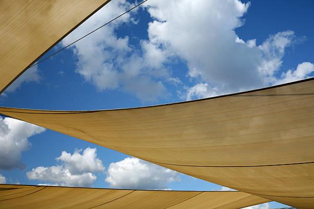 Three sun shade sails against a blue sky stock photo