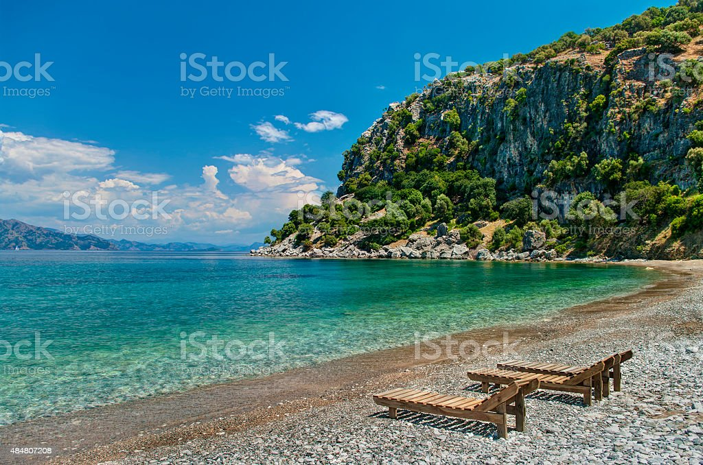 three sunbeds on pebble beach with rocky mountain stock photo