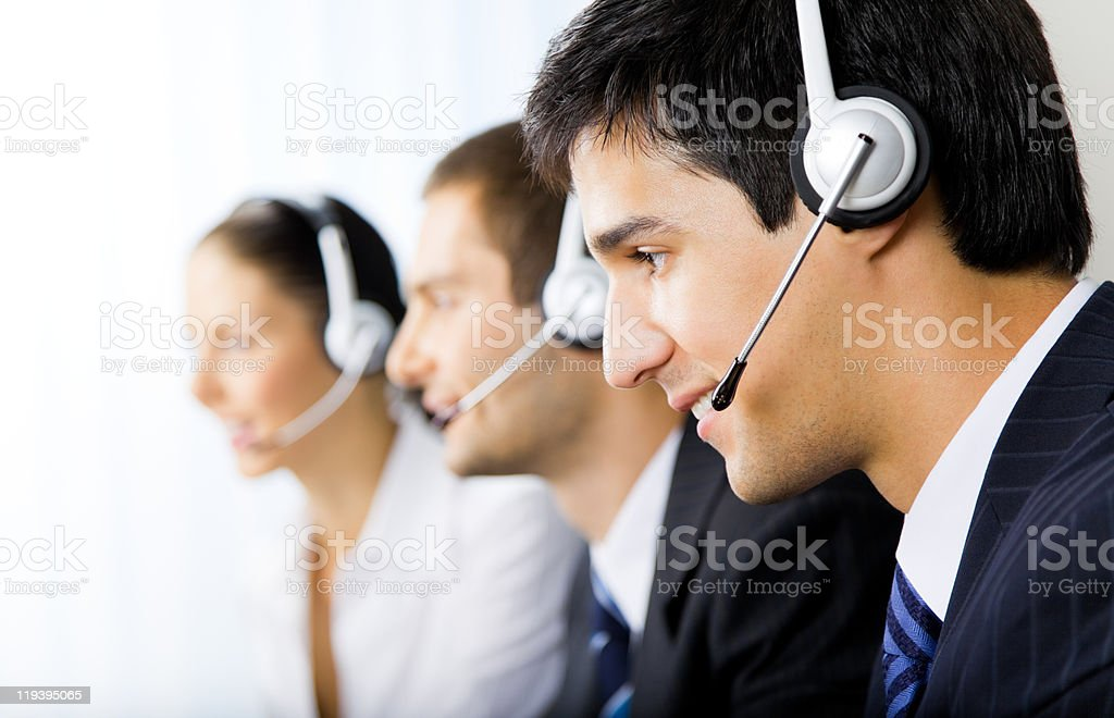 Three support phone operators at workplace stock photo