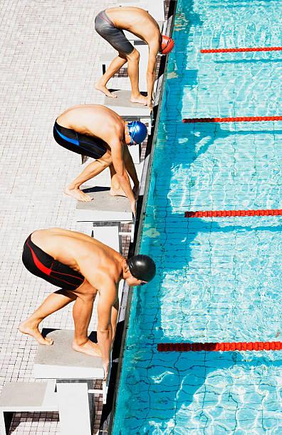 les nageurs utilisent la piscine à partir de trois pâtés de maisons - starting block photos et images de collection