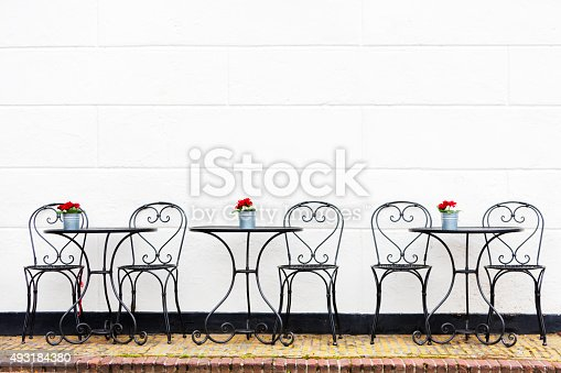three tables with chairs at a street restaurant, white wall in the background with copyspace, Brielle, Netherlands