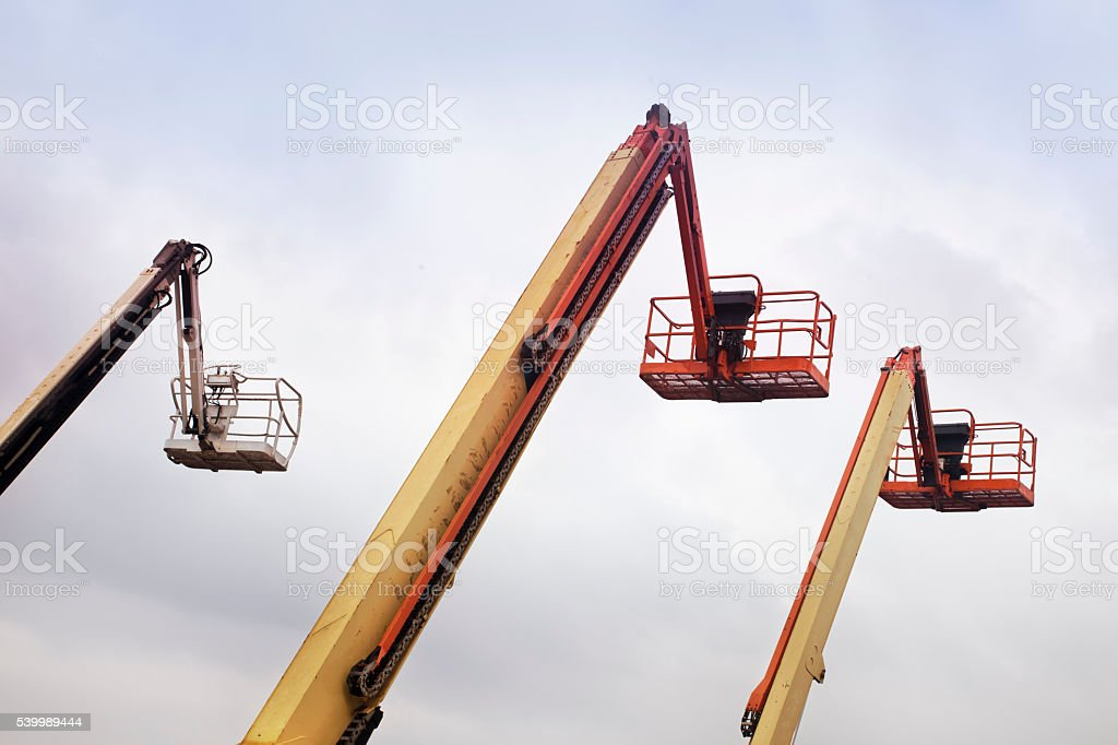 Three tall cherry pickers. stock photo