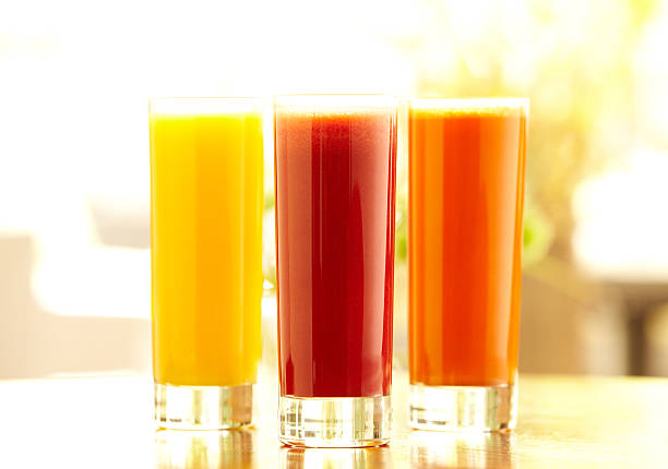 Three tall glasses of orange, carrot and vegetable juice Bright still life shot of three types of juice: orange, carrot and vegetable in tall glasses sitting on a bar counter in a restaurant.  Horizontal shot. vegetable juice stock pictures, royalty-free photos & images