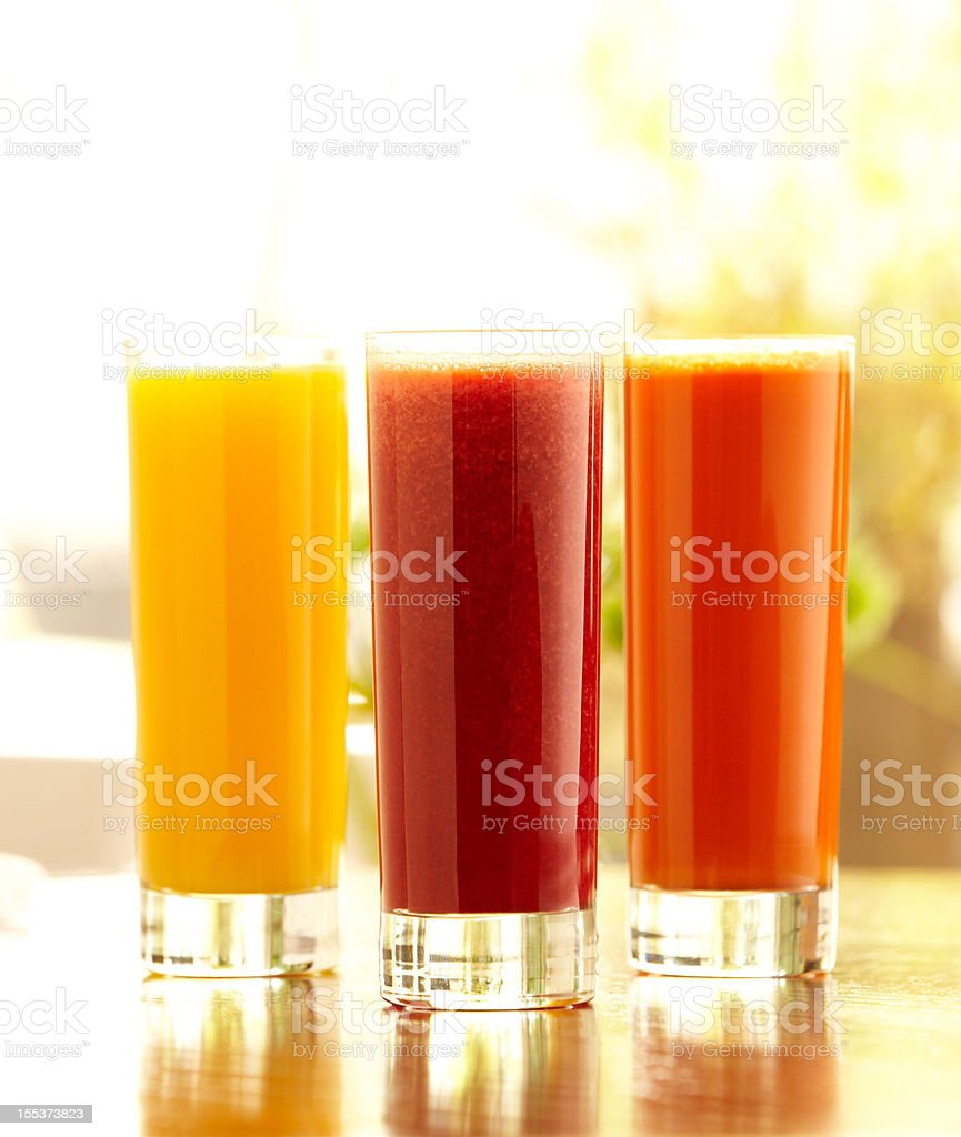 Three tall glasses of orange, carrot and vegetable juice royalty-free stock photo