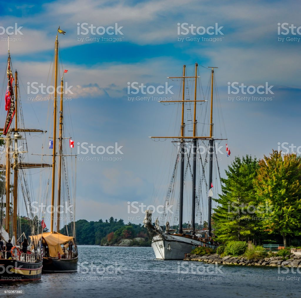 Three Tall Ships moored at the entrance to Brockville Municipal Harbour with a lightly clouded blue sky stock photo