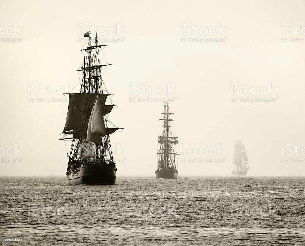 Three Tall Ships Sail in Light Fog royalty-free stock photo