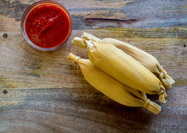 Three tamales on wooden table top view stock photo