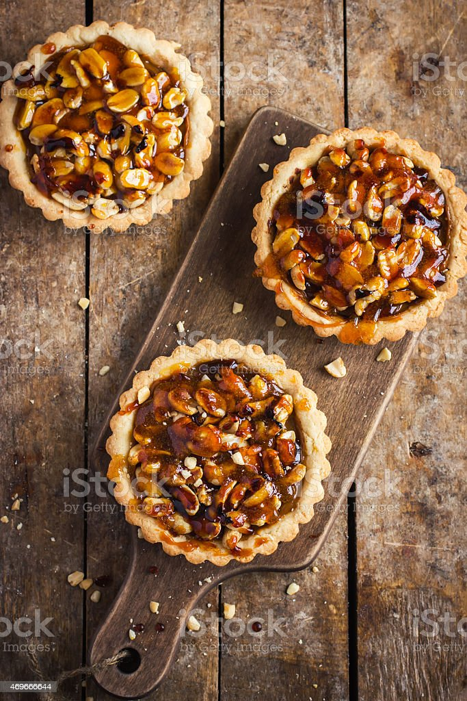Three tart pies on a wooden paddle and wooden surface stock photo