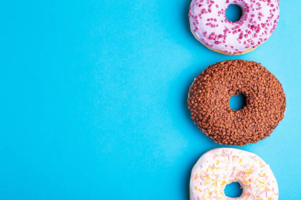Drei schmeckt Donuts: Beeren, Schokolade und Vanille auf leuchtend blauem Hintergrund – Foto