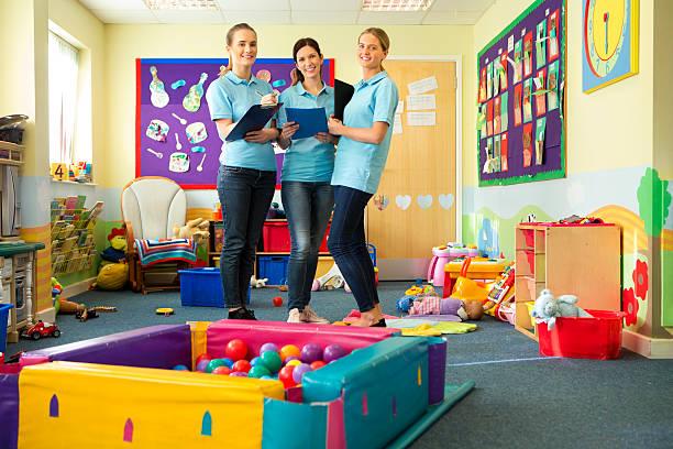 drei lehrer in einem klassenzimmer lächelnd baby stand - erzieherin stock-fotos und bilder