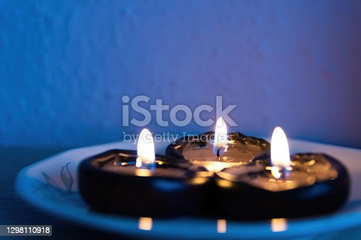 three tealights on a plate in selective focus
