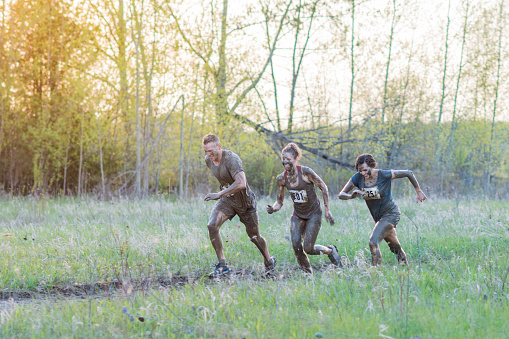 687723318 istock photo Three Teammates During Mud Run 687723588