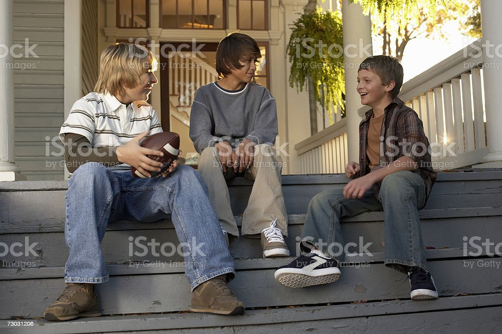 Three teenage boys (13-14) sitting on house steps, holding american football, royalty-free stock photo