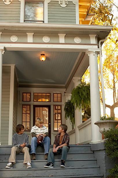 Three teenage boys (13-14) sitting on house steps, holding american football stock photo