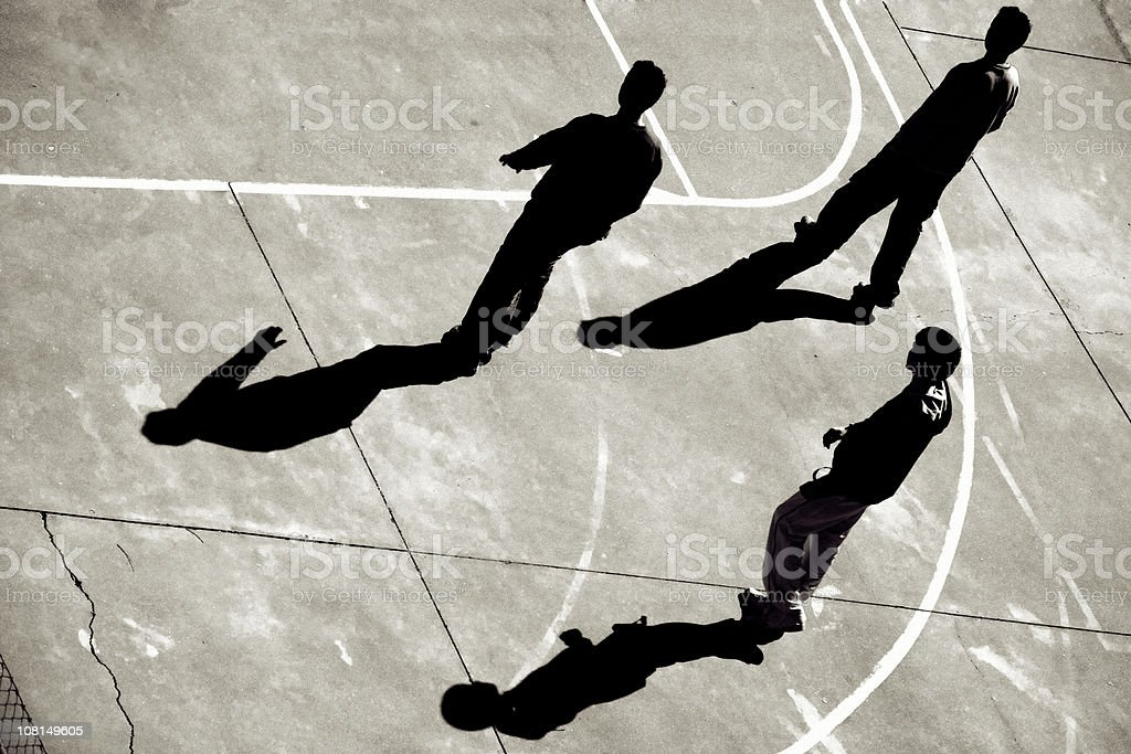 Three Teenage Boys Walking Across Basketball Court stock photo
