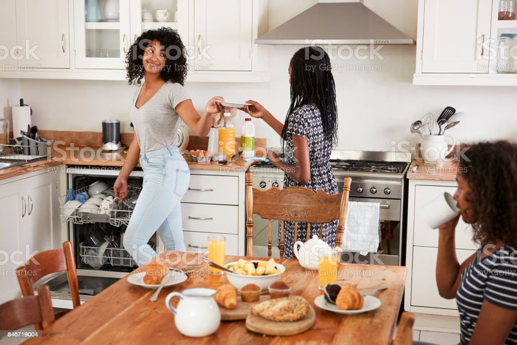 Three Teenage Girls Clearing Table After Family Breakfast stock photo