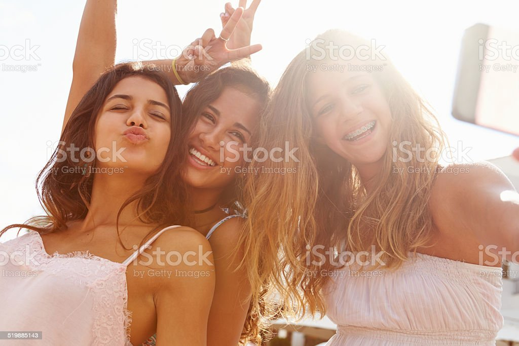 Three Teenage Girls Dancing And Taking Selfie stock photo