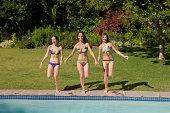 3 つの 10 代の少女のビキニの屋外プール