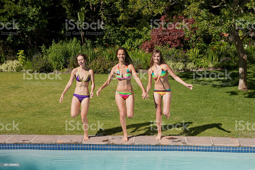 Three teenage girls in bikinis in outdoor pool stock photo