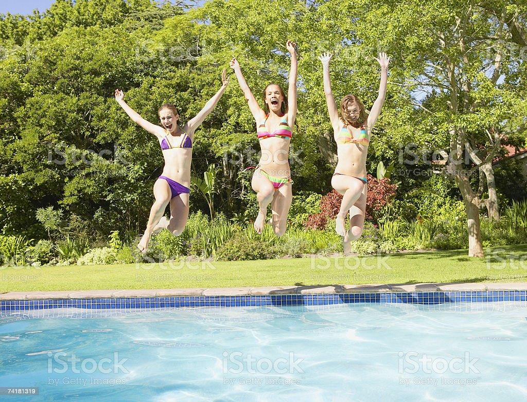 Three teenage girls jumping into pool stock photo