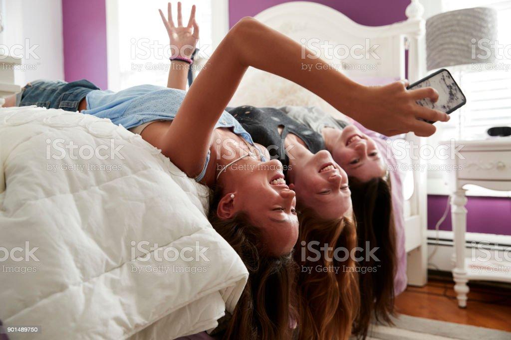 Three teenage girls lying on bed taking a selfie upside down stock photo