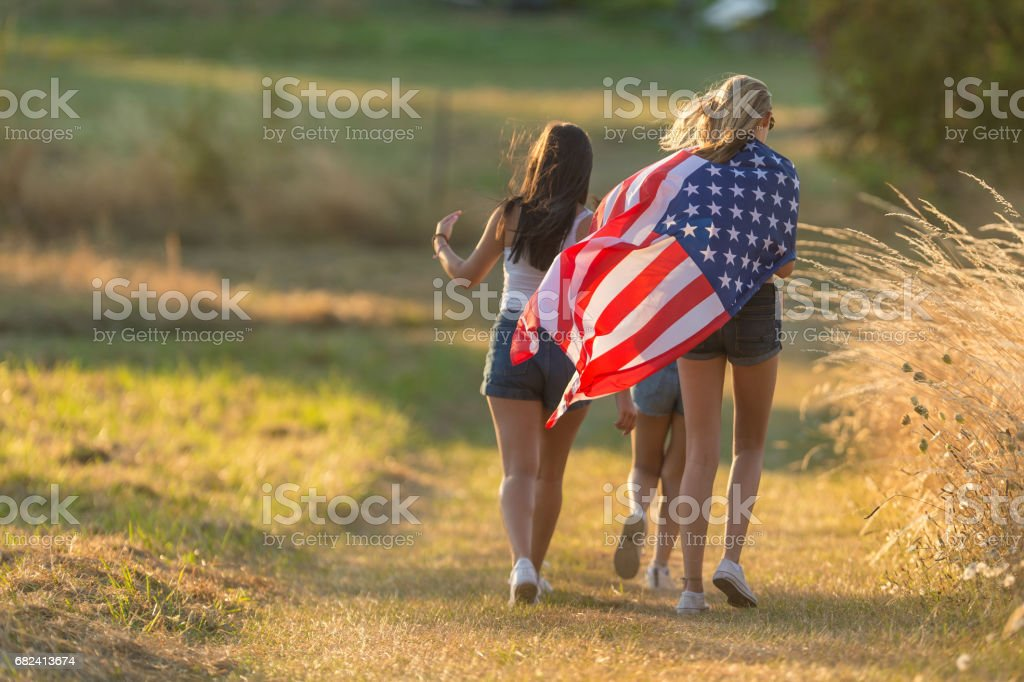 Three teenage girls running down footpath with American flag royalty-free stock photo